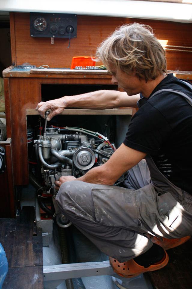Hombre haciendo mantenimiento de motor en un barco